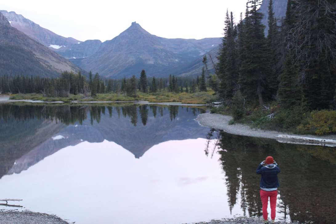 a person takes a picture of mountains reflected in a mirror-still lake